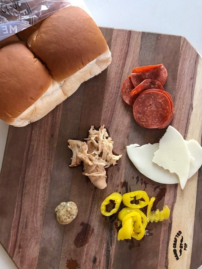 Loaded with flavors, these yummy, and so easy, Italian Chicken Sliders are one of my family's favorite dinner recipes! Pepperoni, chicken, banana peppers and an Italian dressing - yum!!