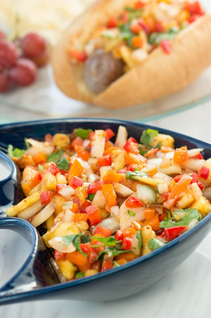 This pineapple relish will be the perfect garnish for all your favorite recipes! Serve it on top of brats, hamburgers, chicken, steak, or fish! Yummy side dish to add to your picnic or dinner recipe! If you're looking to make something special for dad this year, look no further than Bratwurst with pineapple relish garnish! It will fill his craving for meat and be a dinner he'll remember. You don't even have to head to the grill to pull off this amazing meal. This pineapple relish will be the perfect garnish for all your favorite recipes! Serve it on top of brats, hamburgers, chicken, steak, or fish! Yummy side dish to add to your picnic or dinner recipes! Bratwursts with a Pineapple Relish Garnish Pineapple Relish Recipe Bratwursts with Pineapple Relish Recipe Type: Sides Cuisine: American Author: Janel at A Mom's Take Prep time: 15 mins Total time: 15 mins Serves: 4 cups Ingredients 1 pineapple 1 red bell pepper 1 orange bell pepper 1 small onion 1/2 bushel cilantro 1/4 cup rice vinegar 1/8 cup soy sauce 1/3 cup hot sauce 1/2 cup sugar Juice from 1 lime Crushed red pepper, ground (to taste) Instructions Finely dice pineapple, bell peppers, and onion and add to a bowl. Coarsely chop cilantro, add to your bowl. Add vinegar, soy sauce, hot sauce and sugar. Juice one lime and add it to the bowl. Crush ground pepper with a mortar and pestal, than add it to your pineapple relish. Mix until well combined. Store in the fridge until ready to serve. Use as a relish to top your favorite meats. This pineapple relish will be the perfect garnish for all your favorite recipes! Serve it on top of brats, hamburgers, chicken, steak, or fish! Yummy side dish to add to your picnic or dinner recipes!