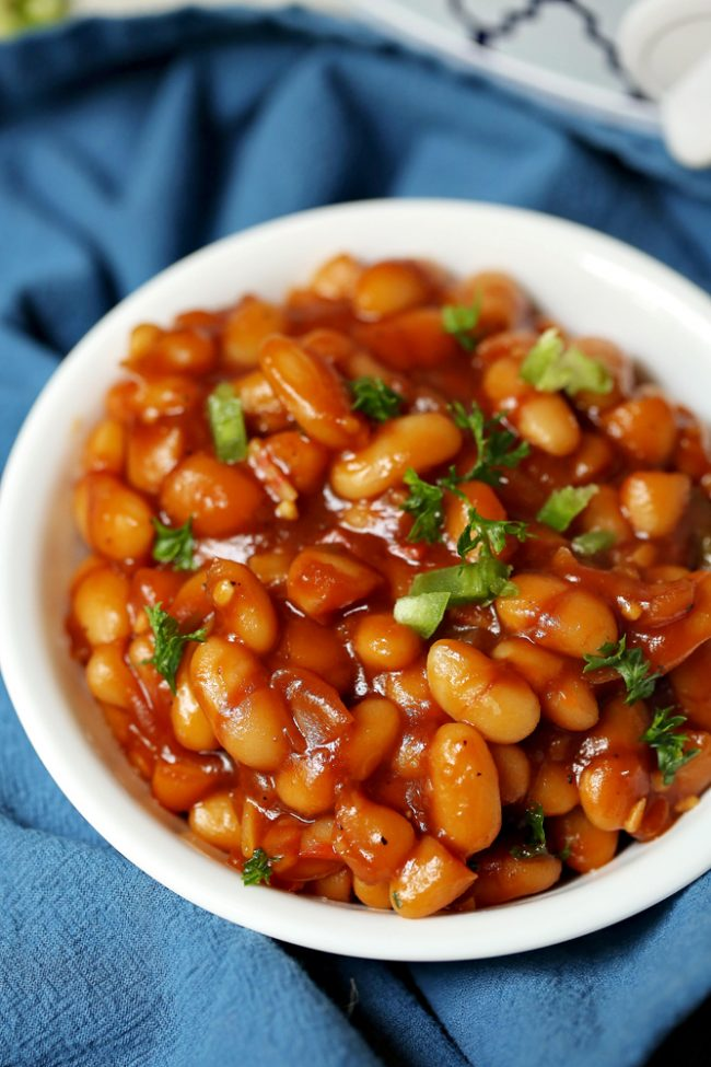 Crockpot barbecue baked beans! So easy to make and even a homemade barbecue sauce recipe! Perfect side dish recipes for any gathering.