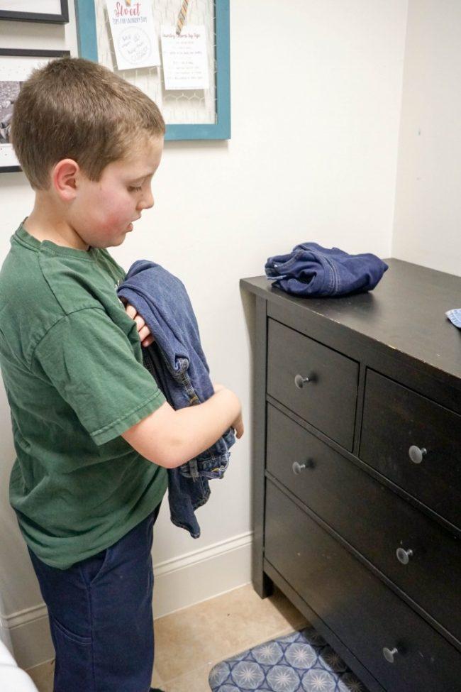 boy folding laundry
