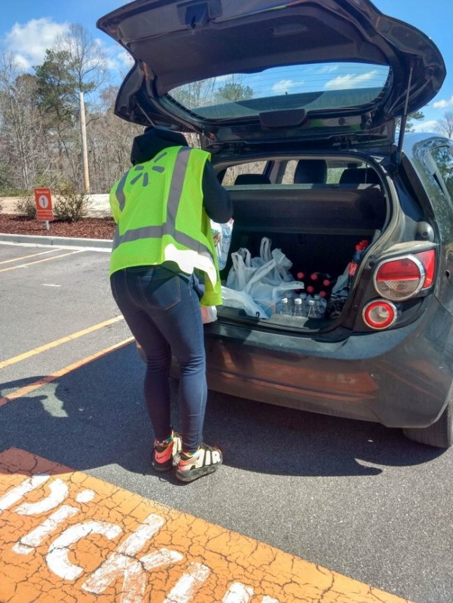 Walmart Grocery Pickup loading groceries into the trunk of a car